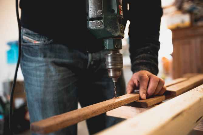 man holding wooden stick while drilling hole